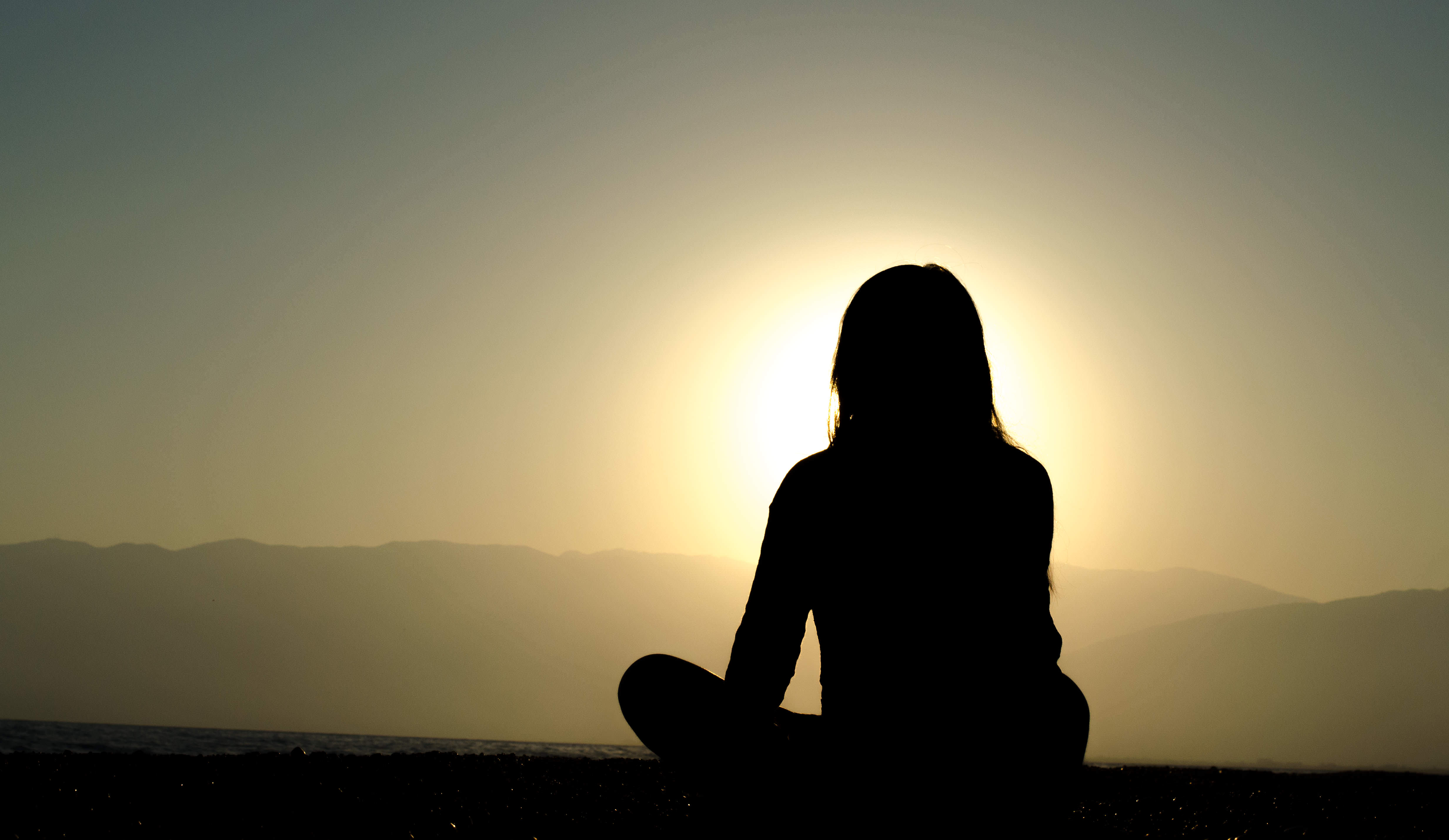 Woman meditating with sun in background