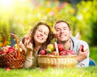 couple eating apples in a field